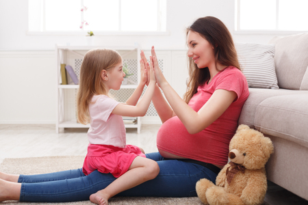 Play clapping hands together with pregnant mom, sitting on floor at home. Family love, motherhood and care concept, copy space.