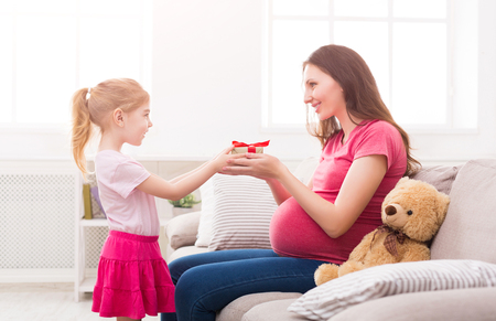 Cute little girl giving her pregnant mother gift at home. Mothers Day celebration, daughter congratulating her mom, copy space. Stock Photo