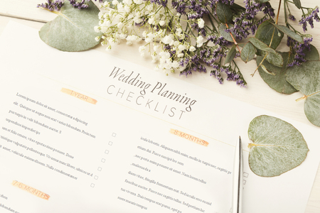 Wedding background with checklist. Paper planner and cute flowers on white wooden table, close up. Love, wedding, celebration, preparation background concept Archivio Fotografico - 95797421