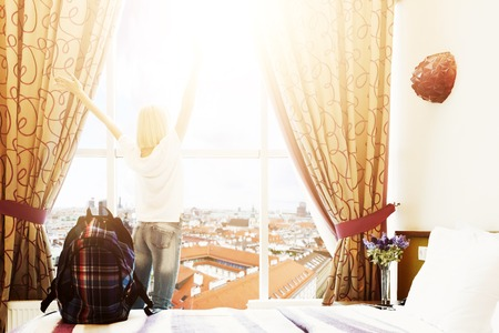 Morning of a new day, woman standing and stretching near the window with city view. She is ready to walk, selective focus on bag, copy space Stock Photo