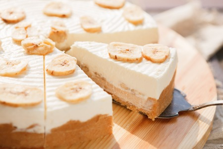 Delicious banana cake on table. Sliced fruit biscuit with caramel and buttercream on wooden catering plate, copy space Foto de archivo
