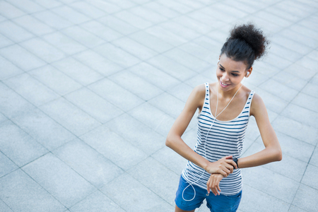 Young smiling african-american woman using smart watch, girl preparing for jogging, copy space