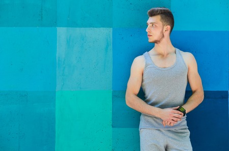 Young sporty man using smart watch, standing at bright blue graffiti wall background, copy space. Modern technology and fitness concept Stock Photo