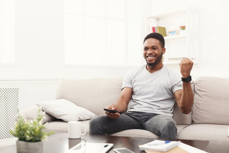Young african-american man watching tv on the couch, happy of favourite football team, pointing with remote controller on tv-set, copy space Stockfoto