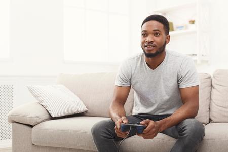 Joven afroamericano jugando videojuegos en casa. Feliz chico sentado en el sofá con joystick en manos, espacio de copia Foto de archivo - 96297262