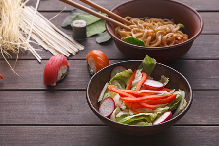 Salad with onion, pepper and radish, rice noodles with soy sauce in bowl and sushi on wooden background. Archivio Fotografico