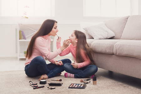 Mother and daughter doing makeup sitting on the floor in the bedroom. Mothers Day, relationship, motherhood, joint activities and interests, trust, support, caress, maternal warmth, caring concept 版權商用圖片 - 96299095