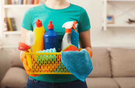 Young woman holding bucket with cleaning items, sponges and rags in hands, close up. Household equipment, spring-cleaning, tidying up, cleaning service concept, copy space Stock Photo
