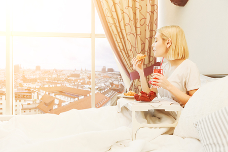 Beautiful young woman sitting on bed in sunny hotel room with beautiful city view. Traveller having healthy breakfast, eating croissant and drinking juice, copy space