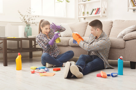 Young couple spring-cleaning and having fun. Happy family with spray detergents and various household equipment sitting on the floor in home interior. Housekeeping and cleaning service concept Stock Photo