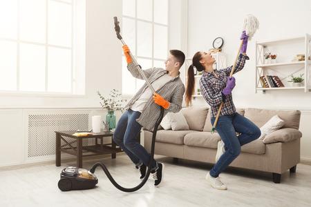 Joven pareja limpiando el hogar, jugando con un trapeador y una aspiradora, divirtiéndose en la sala de estar. Concepto de limpieza y limpieza del hogar Foto de archivo