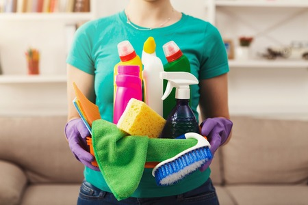 Young woman holding bucket with group of cleaning supplies for natural and environmentally friendly cleaning. Household equipment, spring-cleaning, tidying up, cleaning service concept, copy space