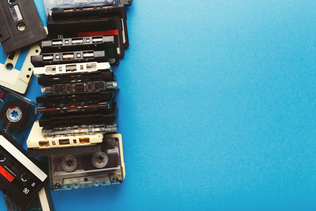 Creative border of vintage cassettes. Old retro tapes on blue background, top view with copy space, multimedia concept Imagens