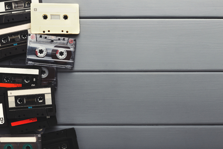 Creative border of vintage audio cassettes. Old retro tapes on gray wooden planks background, top view with copy space, multimedia and music lovers concept Imagens