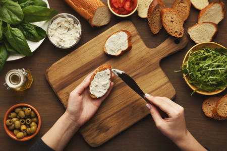 Preparing healthy vegetarian bruschettas on dark rustic wooden table. Top view on female hands spreading soft cheese on rye wholegrain bread. Making vegetable sandwiches for healthy snack