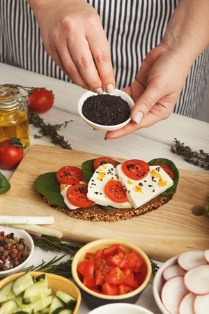Female hands making bruschettas with cheese, tomato, basil and black sesame. Healthy vegetarian sandwiches at kitchen table with various vegetable bowls and greens. Cooking food background, closeup