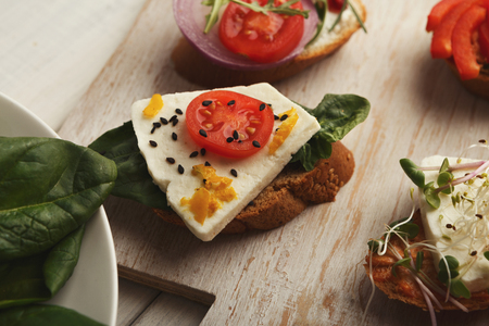 Right snack for morning meals. Crusty toast with tomato, basil and cheese. Healthy breakfast on wooden board closeup