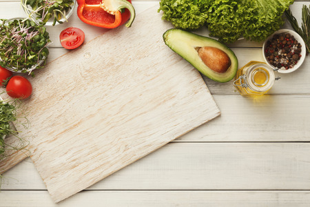 Healthy food preparation background with copy space for recipe. Top view on white wooden cutting board, organic tomatoes, avocado and juicy greens