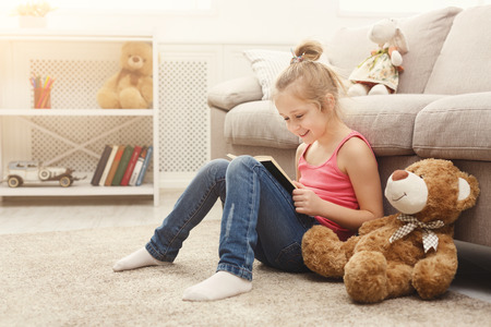 Cute happy little casual girl and her teddy bear reading book. Pretty kid at home, sitting on the floor near sofa with her favorite toy, copy space