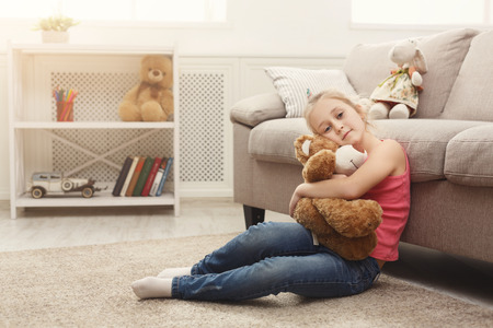 Cute happy little casual girl embracing teddy bear. Pretty kid at home, sitting on the floor near sofa with her favourite toy, copy space