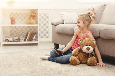 Niña casual viendo la televisión en casa. Niña sentada en la alfombra del piso con su amigo oso de peluche, sosteniendo un control remoto y cambiando de canal