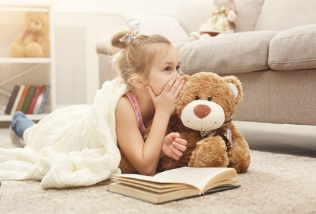 Cute happy little casual girl embracing teddy bear, reading book and sharing secrets with her favorite toy friend. Pretty kid at home, lying on the floor near sofa Stockfoto