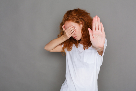 Redhead woman covering her face with palm and saying no. Girl making stop gesture with her hand. Studio shot on gray background, copy space. See no evil and body language concept