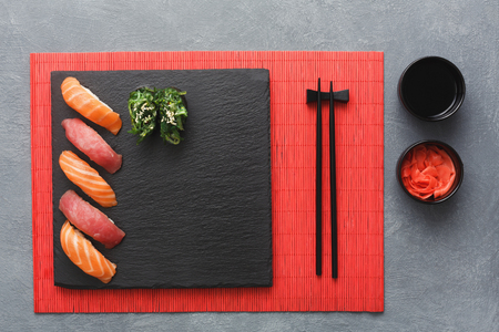 Salmon sushi on black slate plate. Black saucer with soy sauce, ginger in small bowl, chopsticks on red bamboo mat. Flat lay, copy space, grey background, top view Stock Photo