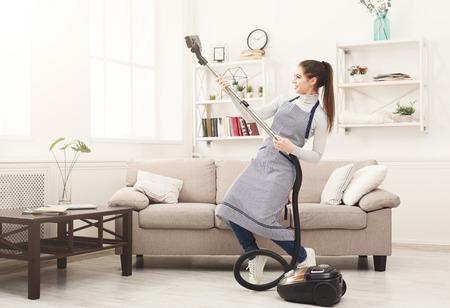 Glückliche Frau, die nach Hause säubert, mit Staubsauger tanzt und Spaß hat, kopieren Raum. Hausarbeit, Hausarbeitkonzept