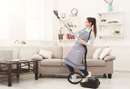 Szczęśliwa kobieta sprzątanie domu, taniec z odkurzaczem i dobra zabawa, kopia przestrzeń. Prace domowe, koncepcja obowiązków domowych