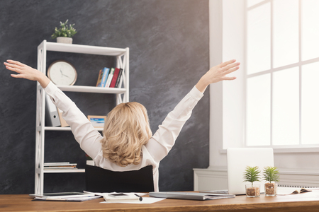 Successful businesswoman resting on office chair with raised hands, copy space, back view