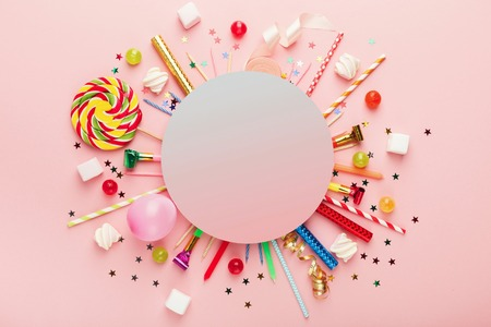 Children birthday party background, frame with sweets and lollipops on pink surface, copy space, top view