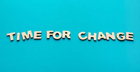 Motivation poster. Phrase Time for change spelled with wooden letters on blue background. Motivation, something new, success and development concept, copy space