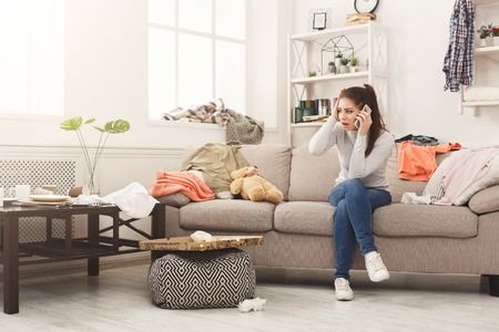 Desperate helpless woman sitting on sofa in messy living room. and talking on mobile, surrounded by many stack of clothes. Disorder and mess at home, copy space Zdjęcie Seryjne - 97184128