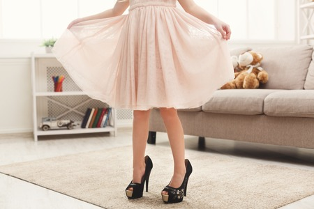 Pretty little girl in mother`s shoes. Small fashionista trying on high heels at home, crop