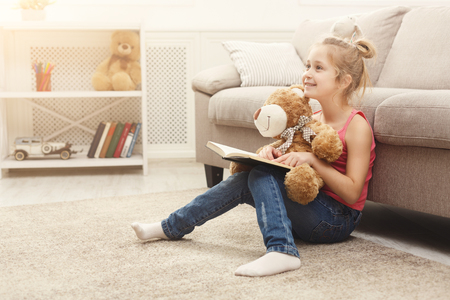 Cute happy little casual girl embracing teddy bear and reading book. Pretty kid at home, sitting on the floor near sofa with her favorite toy, copy space Stockfoto
