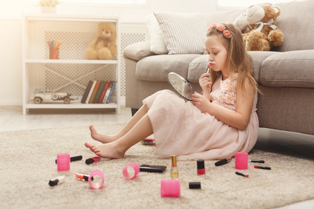 Cute little girl trying her mom`s cosmetics. Pretty kid sitting on the floor carpet among lots of beauty products. Small fashionista doing make up