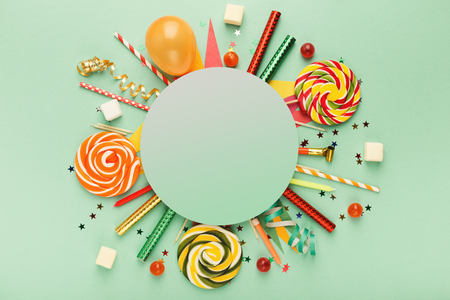 Children birthday party background, frame with sweets and lollipops on green surface, copy space, top view