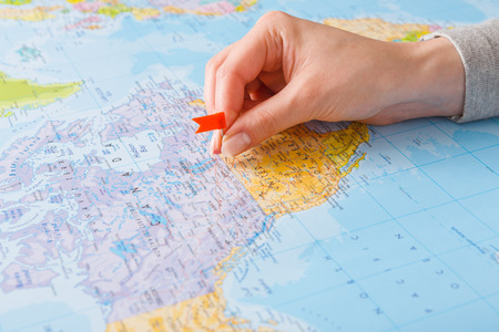 Travelling background. Female hand tackling country with flag-pin on the map. Tourism and vacation concept Archivio Fotografico