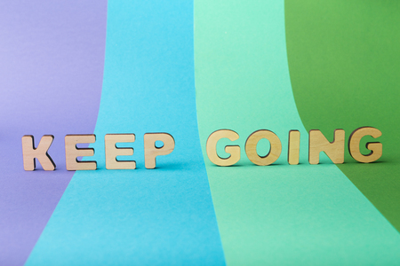 Motivation poster. Phrase Keep going spelled with wooden letters on colorful background. Motivation, never give up, success and development concept, copy space Stock Photo