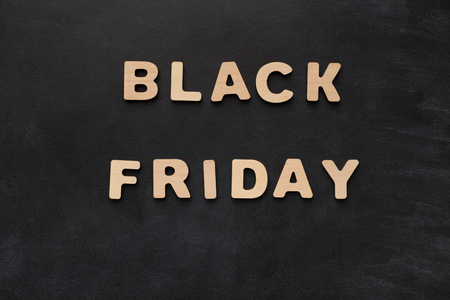 Black Friday inscription on dark background. Wooden letters spelling popular sales phrase. Shopping, marketing, discounts concept, copy space, top view Stok Fotoğraf