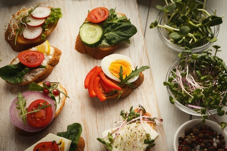 Assortment of healthy vegetarian bruschettas. Various sandwiches with cheese, organic vegetables and microgreens. Tasty food background on white rustic wood, right snack concept