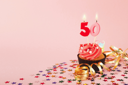 50th birthday cupcake with candles, sprinkles and ribbon on pink background. Card mockup, copy space. Birthday, party, holiday concept