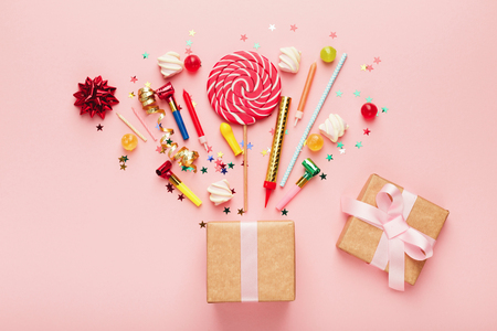 Birthday party background with gifts and firework of confetti, sweets and lollipops on pink surface, copy space, top view. Stockfoto