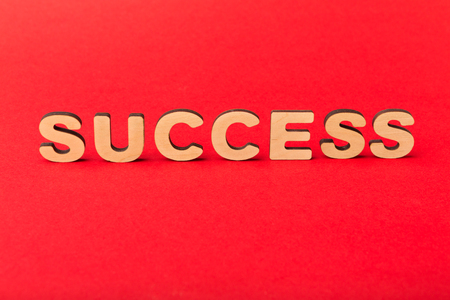 Motivation poster. Word Success spelled with wooden letters on red background. Achievement, progress and development concept, copy space