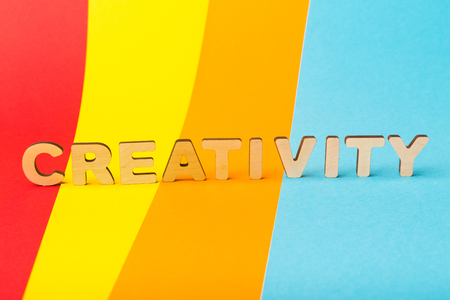 Word Creativity made of wooden letters on colorful background. New idea, innovation, be brave and design concept, copy space
