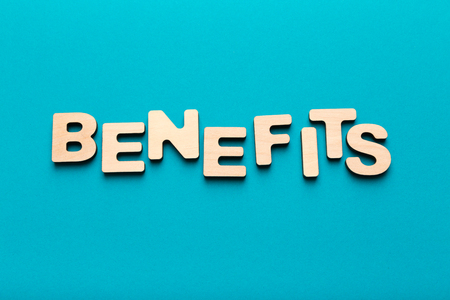 Benefits word inscription made of wooden letters on blue background. Financial health and economics concept, top view, copy space