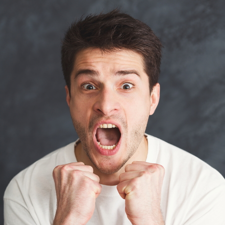 Portrait of angry crying man. Aggressive guy screaming loudly, gray studio background. Psychotherapy exercise