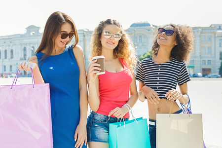 Happy girls with shopping bags outdoors. Smiling female friends in bright summer clothes and wearing sunglasses having a city walk. Friendship, urban lifestyle and leisure concept Stock Photo