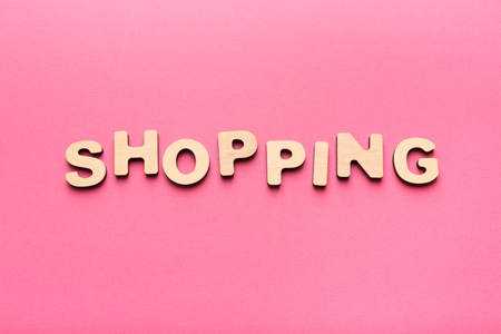 Shopping word on pink background. Top view on wooden letters and red heart, copy space. Trade and marketing concept Stock Photo